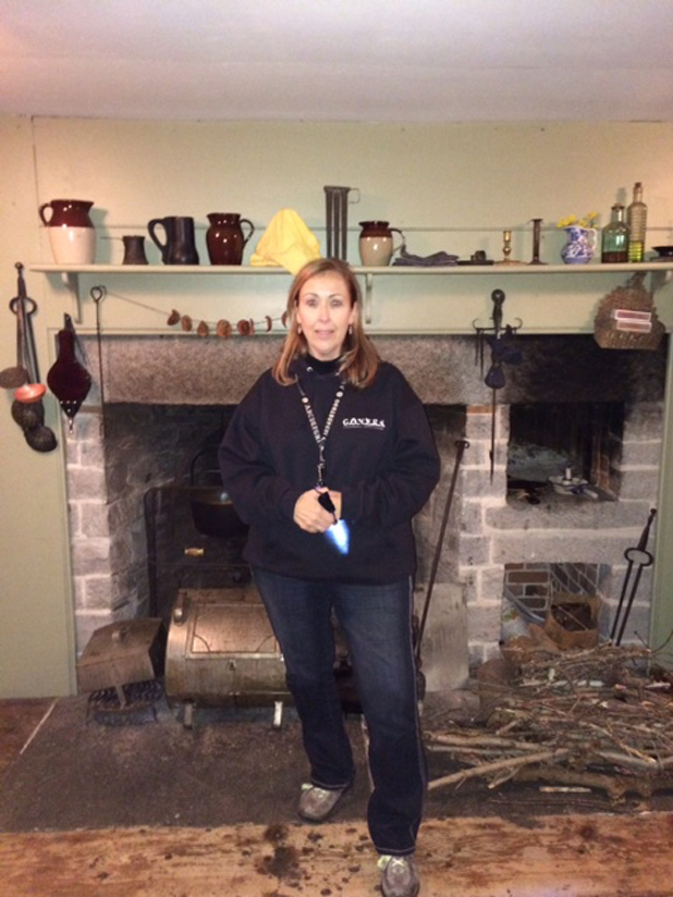 Psychic Medium Karen Hollis stands in front of the hearth at the Nathan Hale Homestead during the investigation