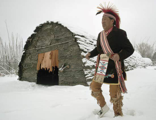 Native American Sachem in front of longhouse